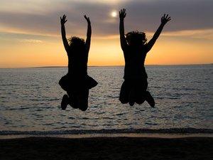 melompat di pantai saat sunset