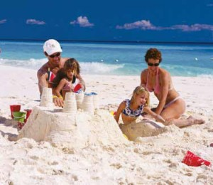 kids and parents building sand castle on beach